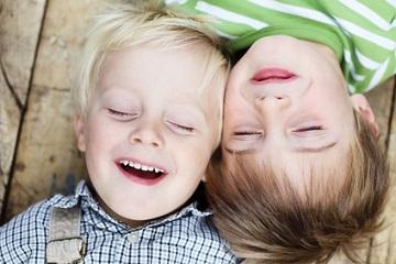 zwei Jungs lächelnd auf dem Boden liegend