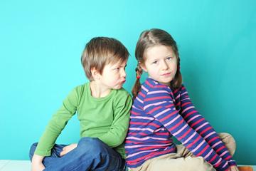 Junge und Mädchen, Geschwister, sehen sich böse an