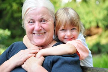 Mädchen umarmt Oma lächelnd von hinten