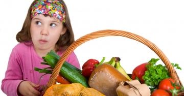 Gesunde Ernährung bei Kindern, Mädchen sitzt vor Obst/Gemüse Korb