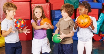 Kinder spielen mit Bällen